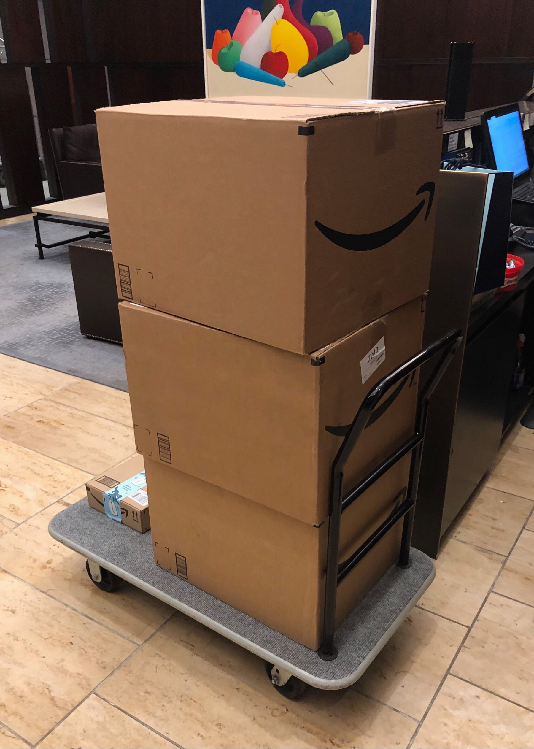 Three large amazon boxes on a rolling cart.