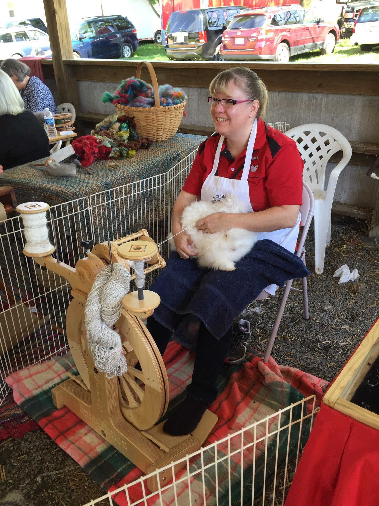 Women spinning yarn straight from an angora rabbit.
