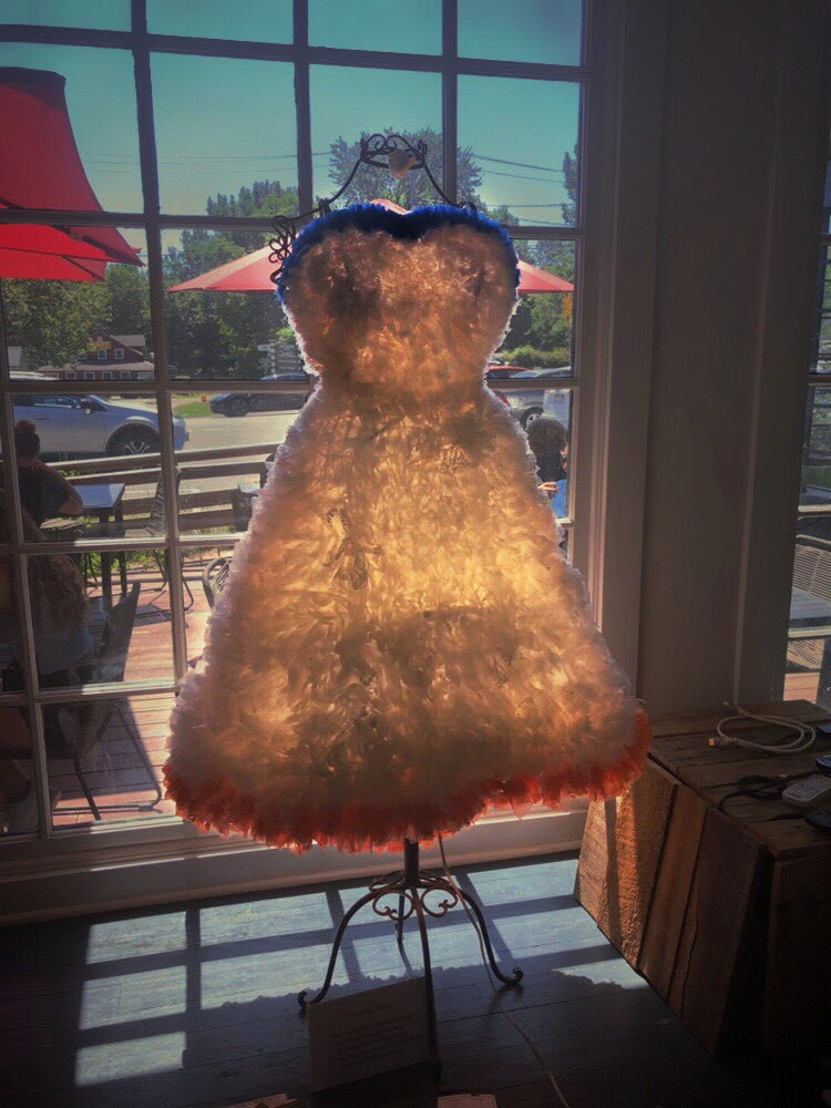Dress made out of plastic bags, glowing from sun through windows.