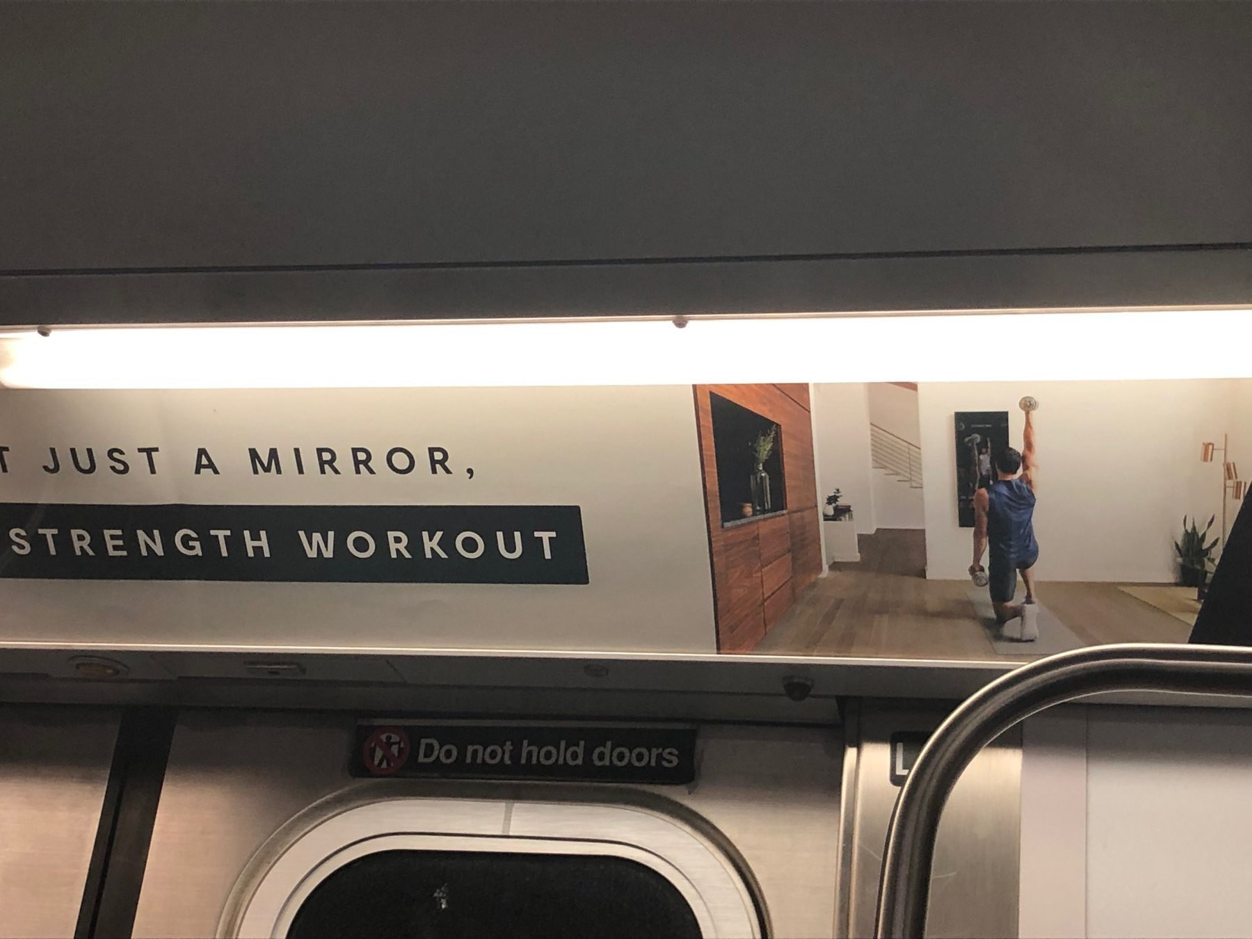 "Subway add for a ""Mirror"" (TM). Apparently a giant smartphone for exercise at home."