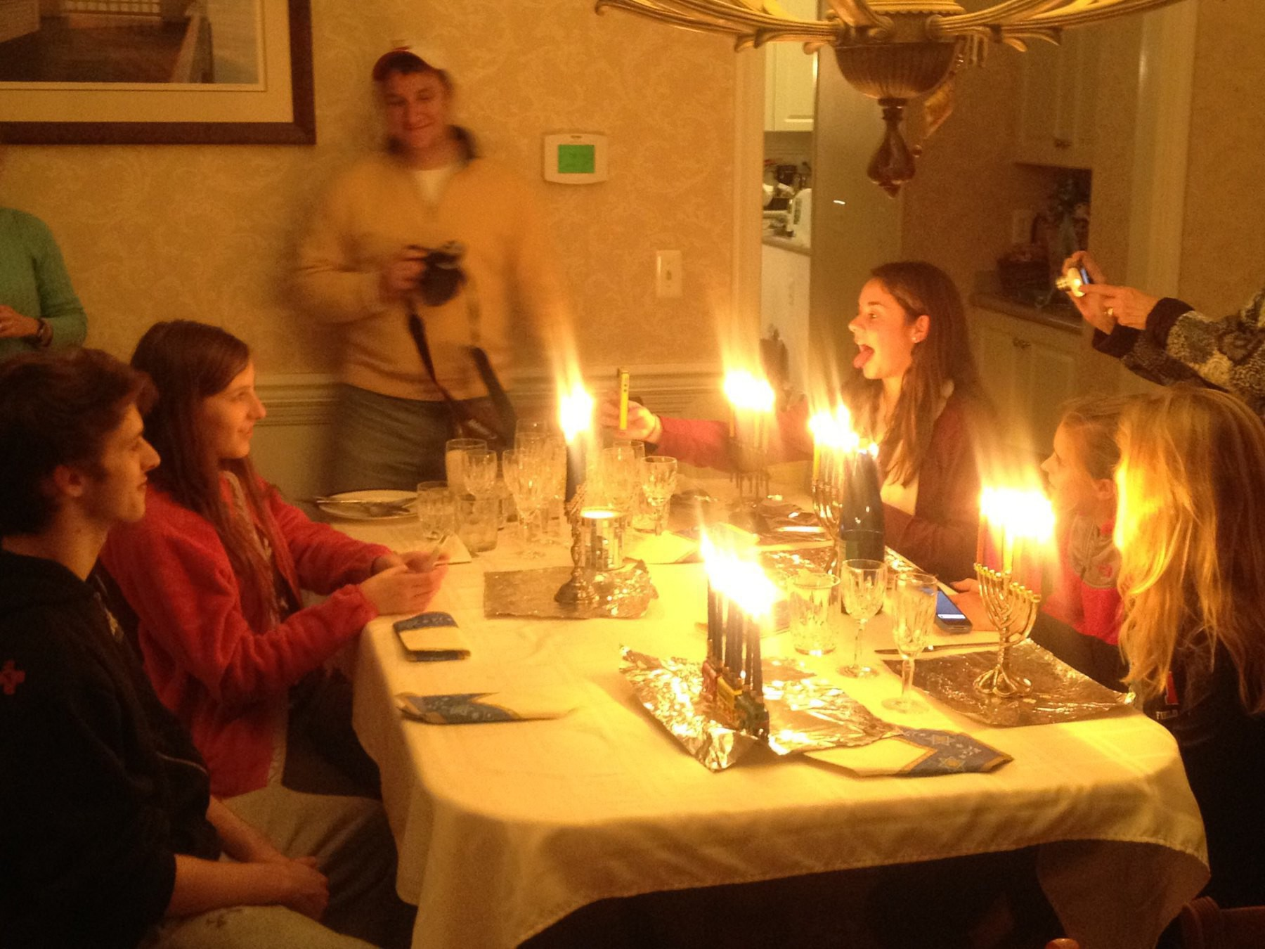 Family at a dining table with a lot of menorahs.