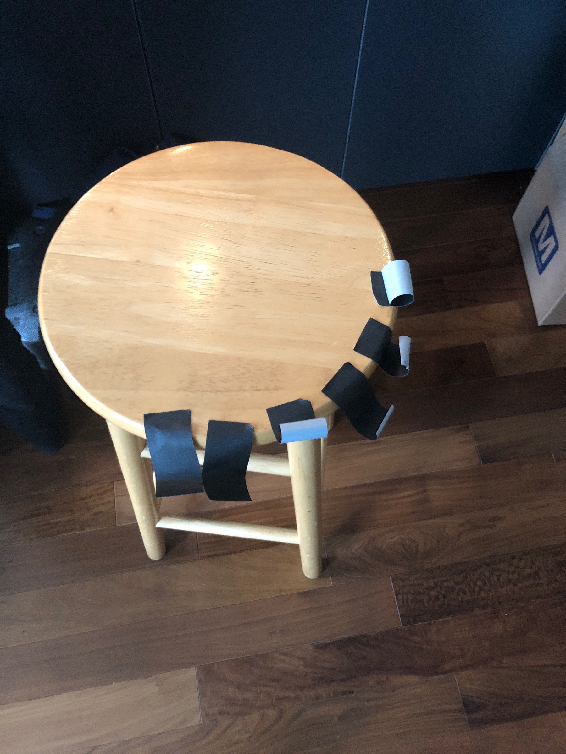 Blonde wooden stool with many small strips of black gaffers tape.