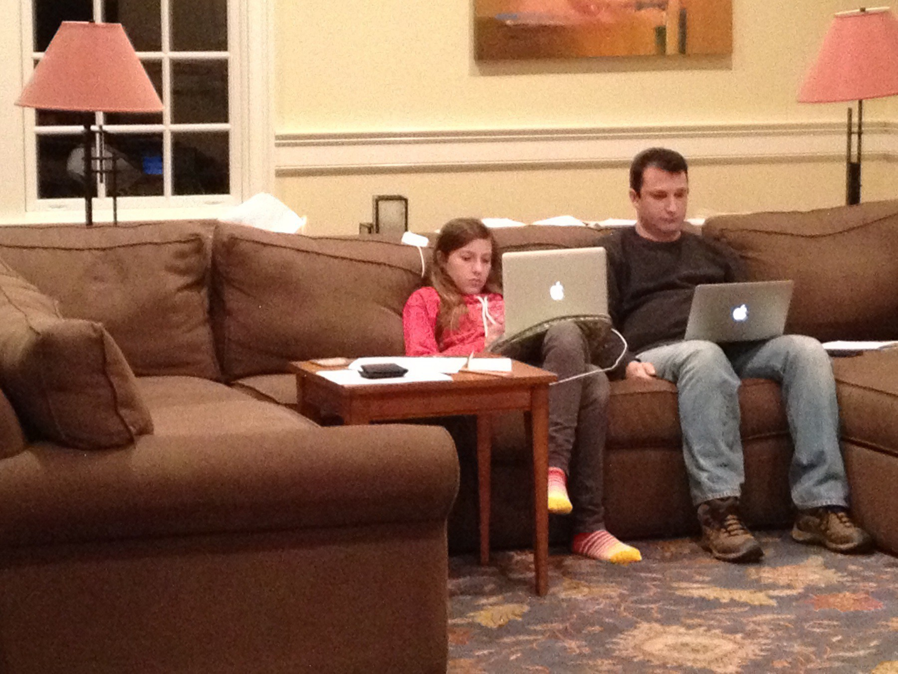 Father and daughter sitting next to each other on a couch. They are both completely focused on their laptops.