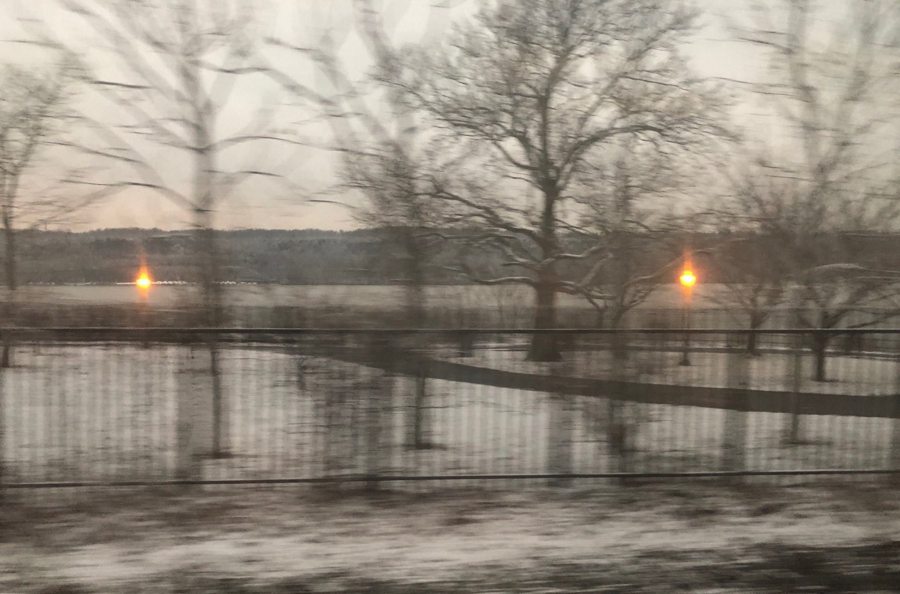 Snowy view of the Hudson river in the early morning from the train. Old fashioned streetlamps are still lit and the trees are bare.