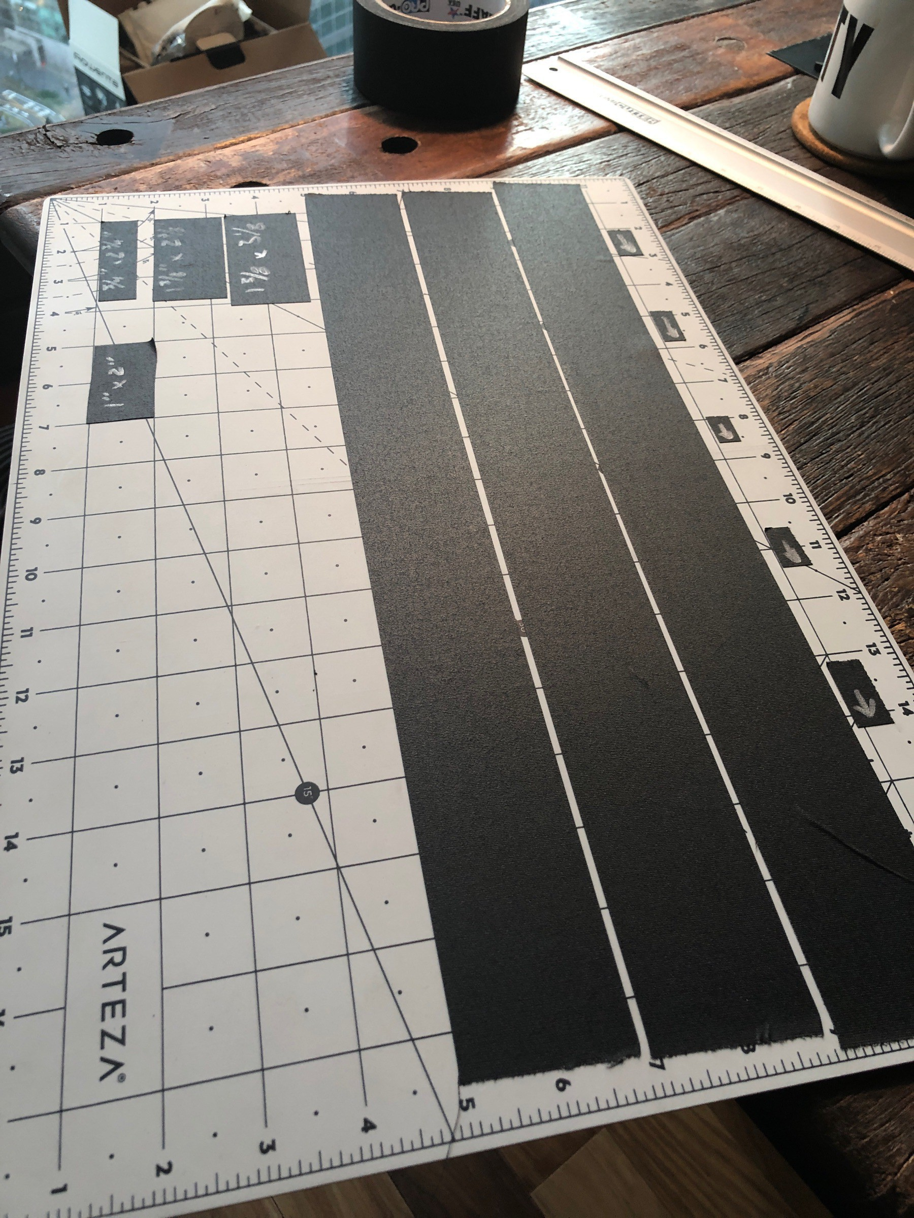 Cutting mat with several strips of black gaffers tape.