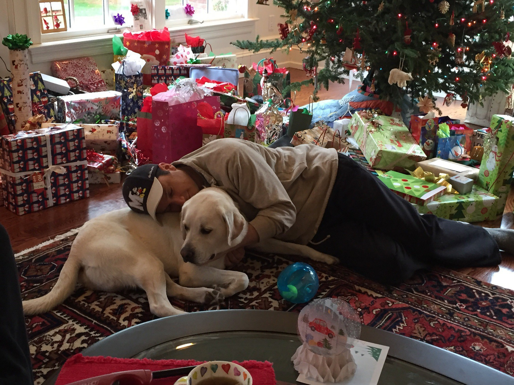 Man is sweetpants cuddling with a yellow lab and surrounded by presents.