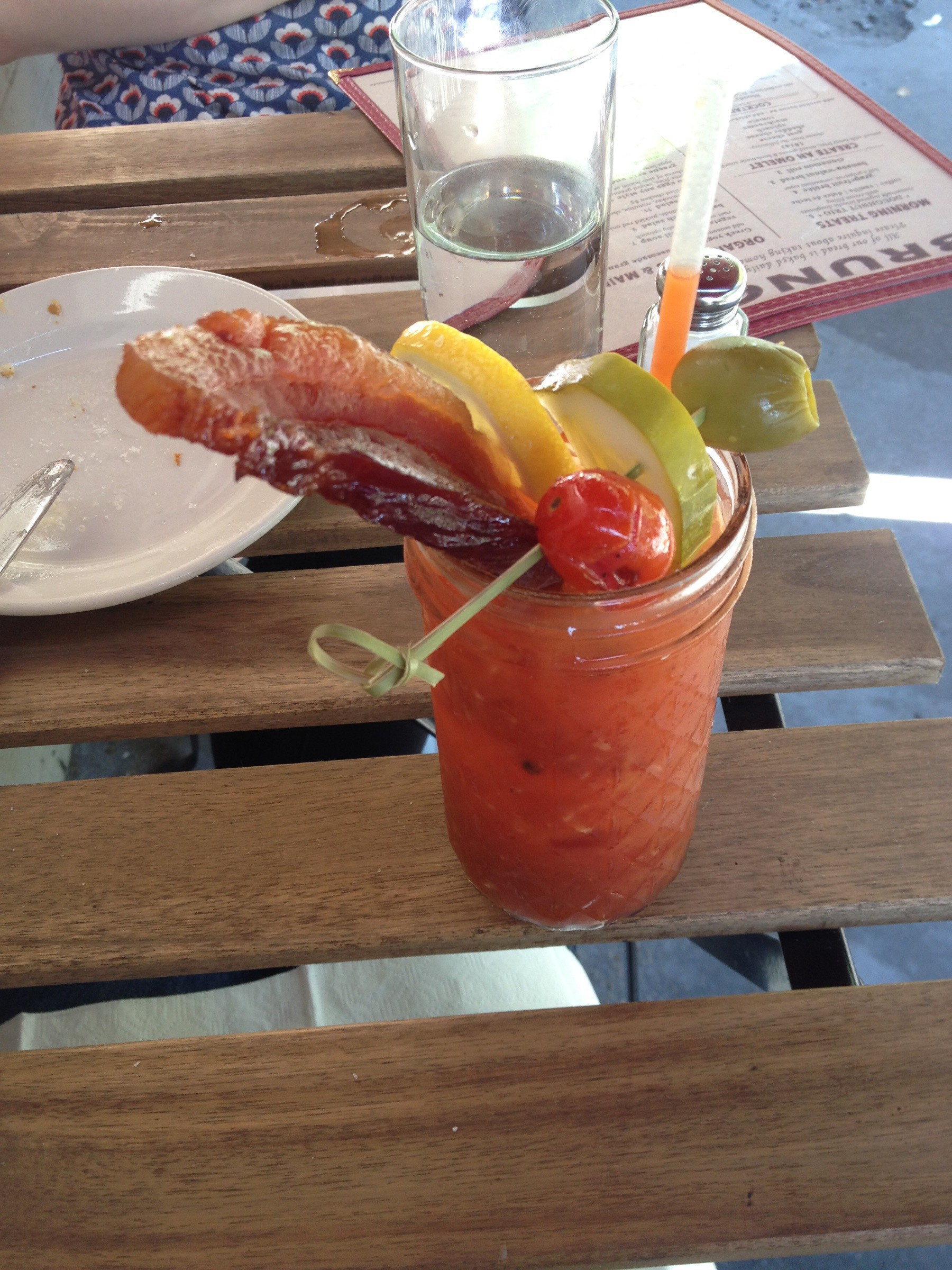 Bloody mary with lots of pickled veggies and bacon. On a picnic bench.