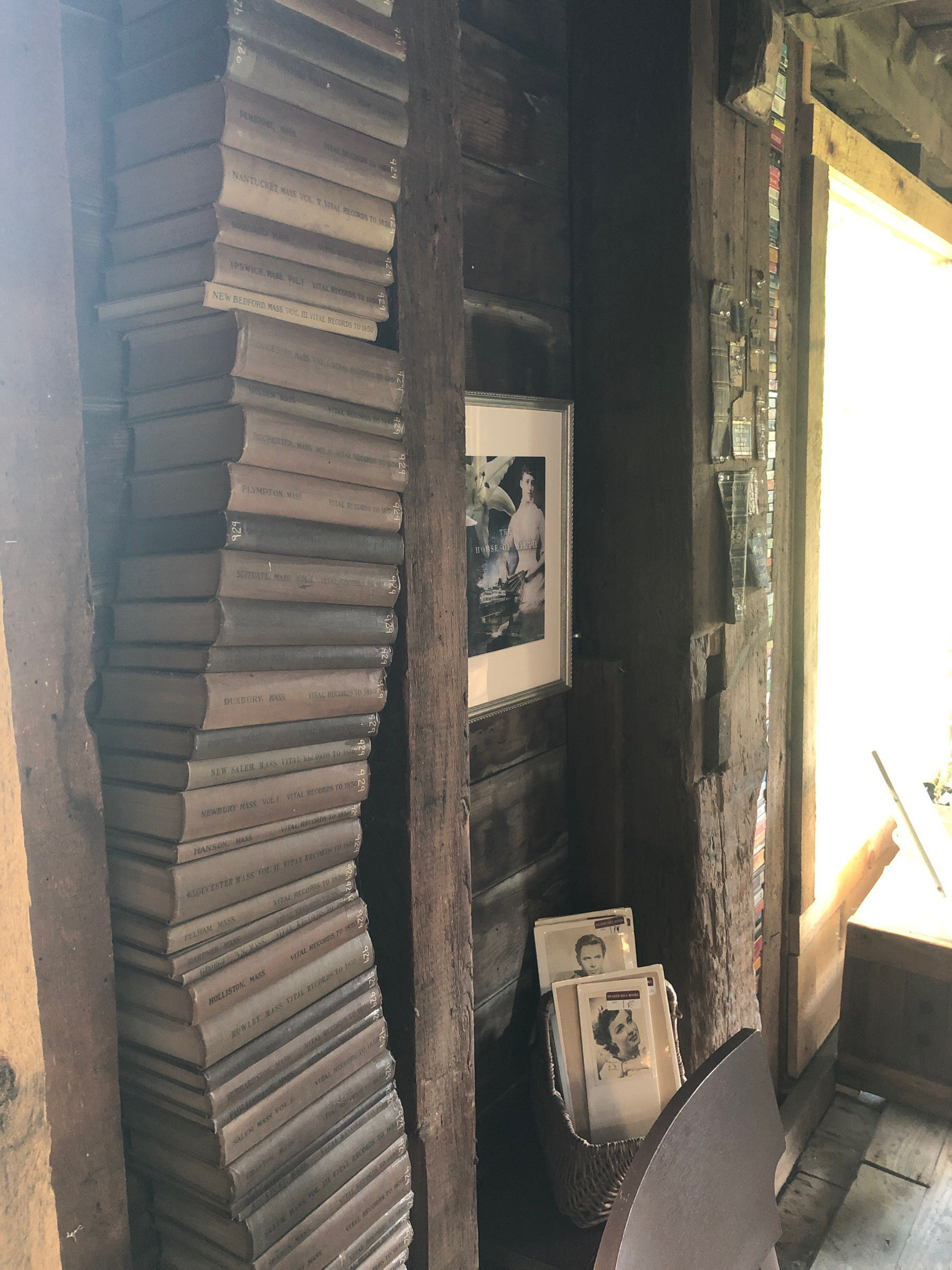 A tall stack of old books in a barn.