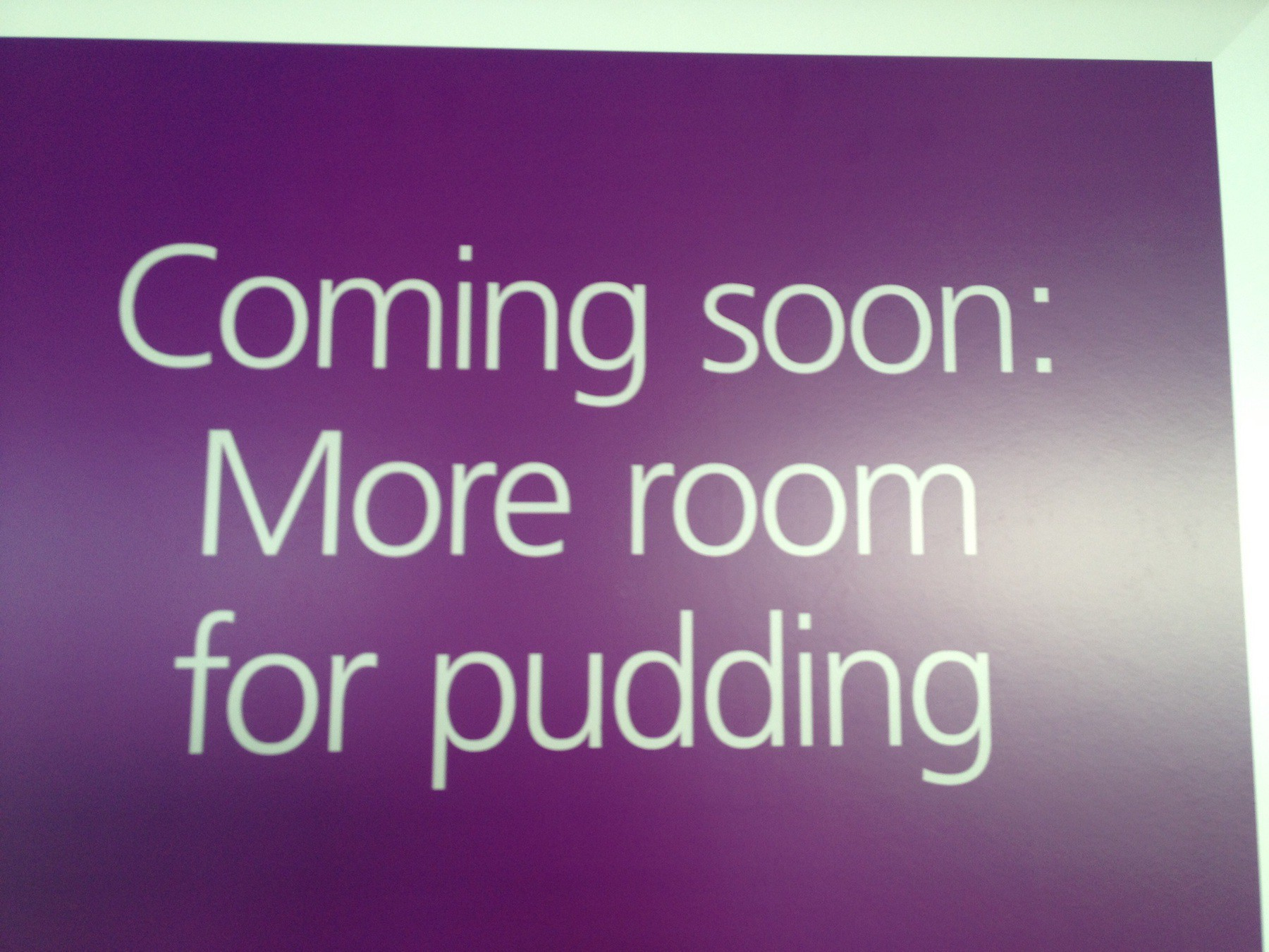 "Purple sign saying, ""Coming Soon: More room for pudding""."