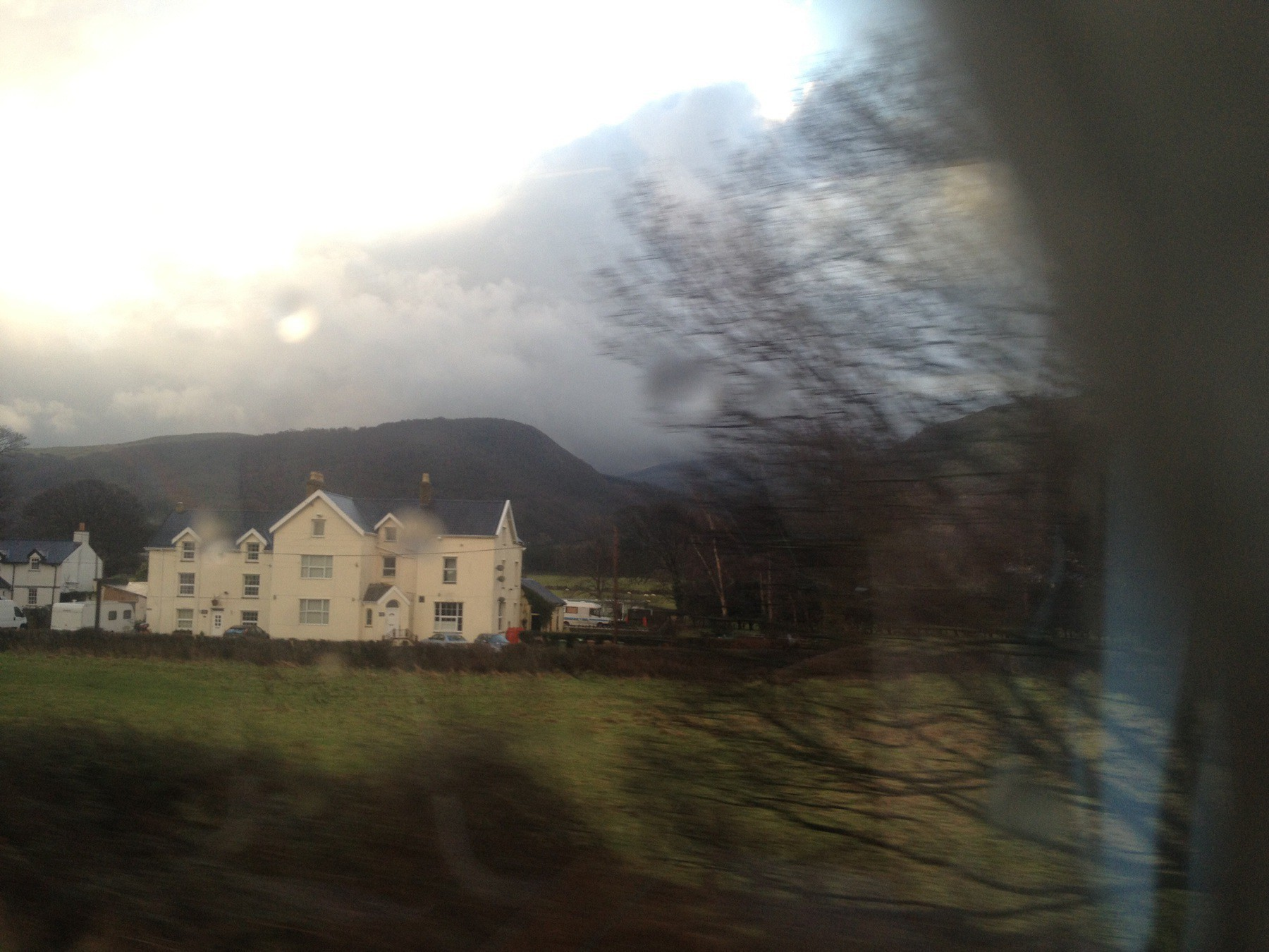 View of manor house, field, and hills through a train window.